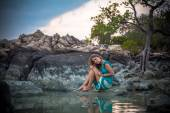 Young beautiful woman in long turquoise dress sitting on a stone by the sea — Stock Photo