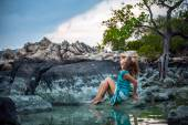 Young beautiful woman in long turquoise dress sitting on a stone by the sea — Stok fotoğraf