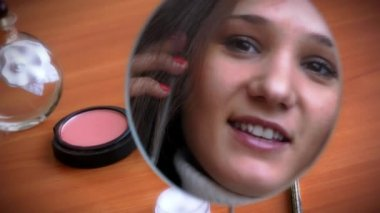 Young beautiful woman talking on phone, looks in mirror and coquettishly smiling herself — Stock Video