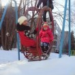 Slow motion of Cute smile happy children swing on winter playground  in the park and sun lighting through Swing boat — Stock Video #75538107