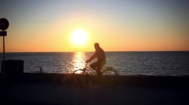 Blurred silhouette of man riding bicycle at beautiful sea during sunset — Vídeo de Stock
