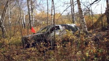 SUV got stuck in the mud and trying to go out in the autumn forest — Stock Video