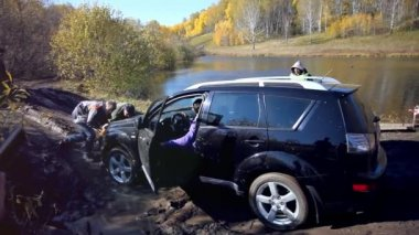 Russia, Siberia, 27 september 2014. SUV got stuck in the mud and trying to go out in the autumn forest. People try to help it — Stock Video