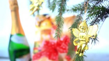 Christmas decoration with gold little angels on branch of spruce, gift and bottle Of champagne — Stock Video