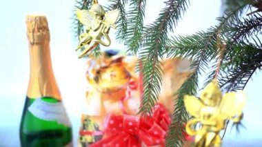 Christmas decoration with gold little angels on branch of spruce, gift and bottle Of champagne. — Stock Video