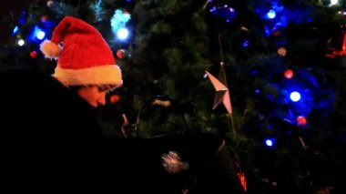Beautiful woman in a fur coat and santa hat near christmas tree receives gift. — Stock Video