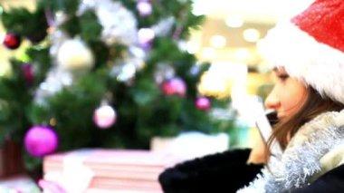 Yong woman in cap Santas talking on the phone near Christmas tree. — Stock Video