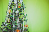 Christmas tree with cones decorated toys on green background — Stock Photo