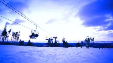 Station de ski de montagne avec les skieurs et les snowboarders. Nature avec le ciel et le déplacement des nuages. Blizzard sur la forêt d'hiver — Vidéo