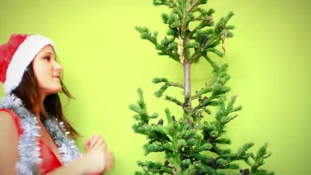 Chica adolescente hermoso sombrero de invierno decorando el árbol de Navidad sobre fondo verde — Vídeo de stock
