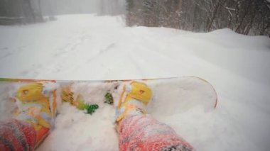 Snowboarder sitting in the mountains during a snowfall at blizzard . view of his boots and board — Stock Video