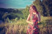 Young red-haired woman on the rock near river is fashionable poses in sunset time — Stock Photo