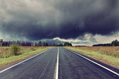 Road and dark thunder clouds — Stock Photo