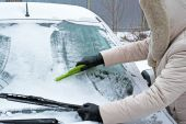 Woman remove snow from windshield — Stock Photo