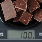 Broken dark chocolate on kitchen scale — Stock Photo #61202513