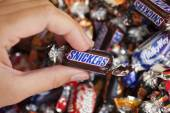 Snickers candy in woman's hand — Stock Photo