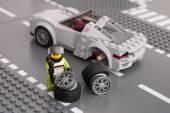Lego driver is fixing wheel of Porsche 918 Spyder — Stock Photo
