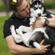 Young man with his dog in his arms,husky puppy — Stock Photo #71968475