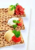 Whole grain crispbread with various toppings — Stock Photo
