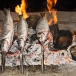 Cooking fish grilled over hot coals bonfire — Stock Photo #53860203