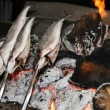 Cooking fish grilled over hot coals bonfire — Stock Photo #53860257