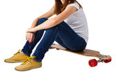 Young woman sitting on a skateboard — Stock Photo