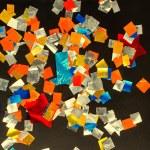 Colored confetti falling on a dark floor — Stock Photo #65229109