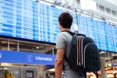 Guy near airline schedule — Stock Photo