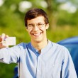 Happy young man showing his driving license — Stock Photo #60468301