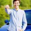 Young man holding key of his new car — Stock Photo #60468367