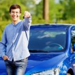Young man holding key of his new car — Stock Photo #60468381