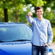 Young man holding key of his new car — Stock Photo #60468407