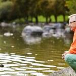 Mature man crouching near pond — Stock Photo #70194657