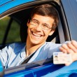 Guy shows driving license from car — Stock Photo #70431383