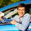 Guy shows driving license from car — Stock Photo #70431943