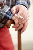 Hands with cigarette on cane — Stock Photo