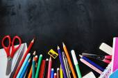 School supplies on blackboard — Stock Photo