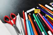 School supplies on blackboard — Stock Photo