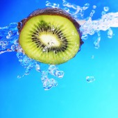 Slice of kiwi in blue water — Stock Photo
