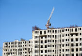 Hoisting tower crane and top of construction building — Stock Photo