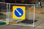 Repair work. Road sign indicating detour hanging on fence — Stock Photo