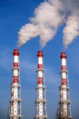 Three striped industrial pipes with smoke over cloudless blue sky — Stock Photo