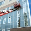 Red construction crane boom in process of finishing office building — Stock Photo #58954103