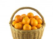 Tangerines in brown wicker basket isolated on white — Stock Photo