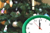 Clock showing twelve hours and dressed up Christmas tree — Stock Photo