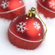 Red Christmas balls with painted snowflakes lying in clean white snow — Stockfoto #61971471