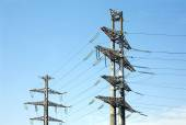 High-voltage power line metal props  over clear cloudless blue sky — Stock Photo