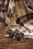 Plaid and slippers on carpet — Stock Photo