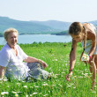 Great grandmother and great granddaughter in meadow — Stock Photo #73499935