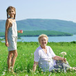 Great grandmother and great granddaughter in meadow — Stock Photo #73530045